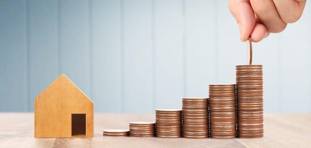 Houten speelgoed huis hypotheek eigendom thuis concept kopen voor familie, munten in de hand