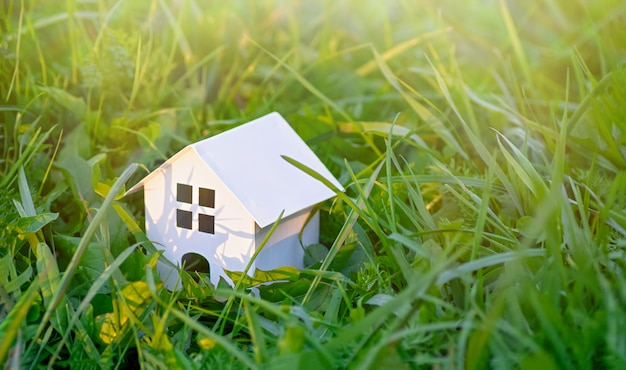 Houten speelgoed huis op een achtergrond van groen gras