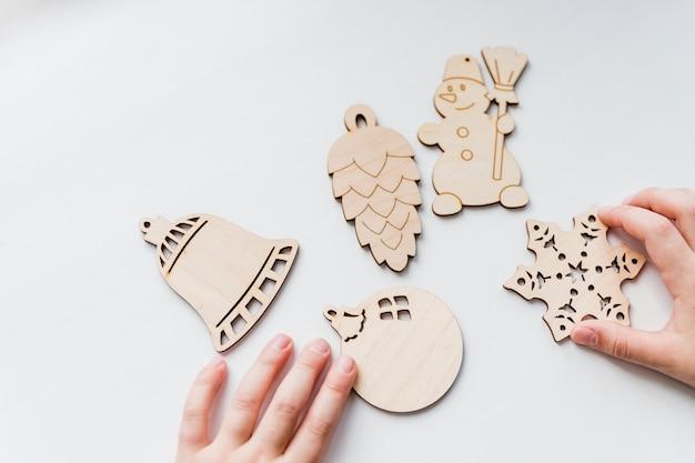Houten speelgoed in handen van kinderen, klaar om kerstversiering te maken. houten kerstboomversieringen op witte achtergrond. hobby, diy, kids vakantie ambachten. kopieer ruimte