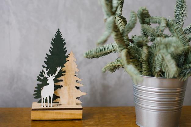 Houten speelgoed: kerstboom en herten op de grijze achtergrond