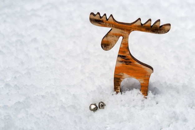 Houten speelgoed kleine herten met klokken op besneeuwde oppervlak