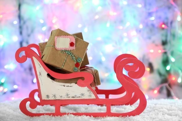 Houten speelgoed slee met kerstcadeaus op glanzend