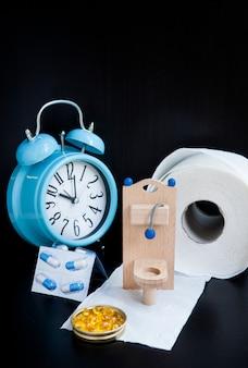 Houten speelgoed toilet, pillen en wekker op zwart