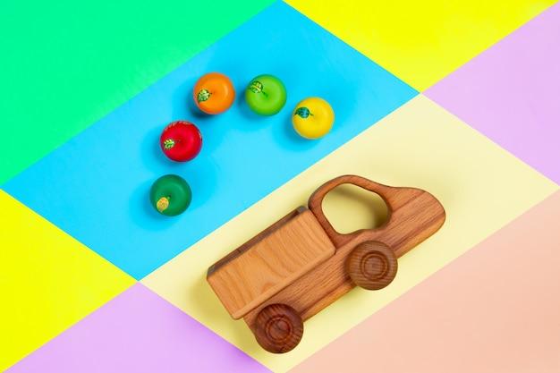 Houten speelgoed vrachtwagens met appels op een geïsoleerde veelkleurige levendige geometrische achtergrond.
