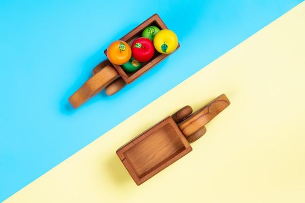 Houten speelgoed vrachtwagens met appels op geïsoleerde achtergrond