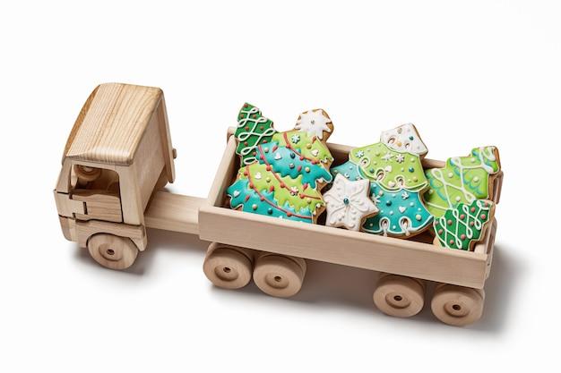 Houten speelgoedauto heeft geluk voor kerstpeperkoek in de vorm van kerstbomen en sneeuwvlokken.