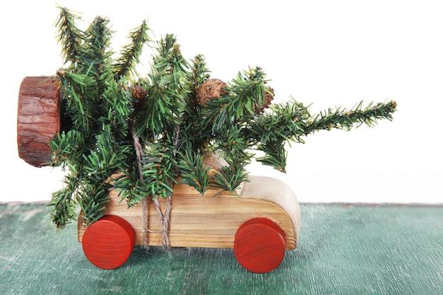 Houten speelgoedauto met kerstboom op een tafel op witte achtergrond
