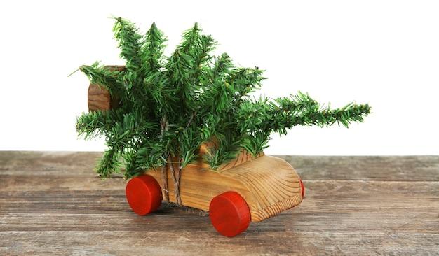Houten speelgoedauto met kerstboom op een tafel over wit