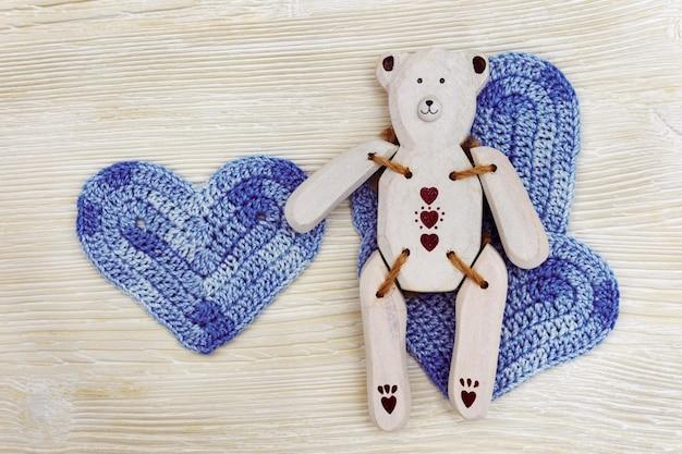 Houten speelgoedbeer met blauw gebreid hart. met de hand gemaakt wit houten toy bear op witte houten achtergrond.
