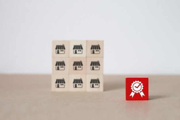 Houten speelgoedblog in kubusvorm gestapeld met kwaliteitssymbool en franchise-marketingpictogrammen slaan achtergrond op.