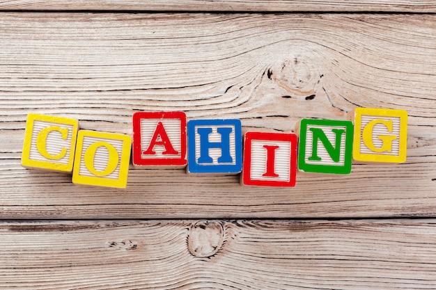 Houten speelgoedblokken met de tekst: coaching