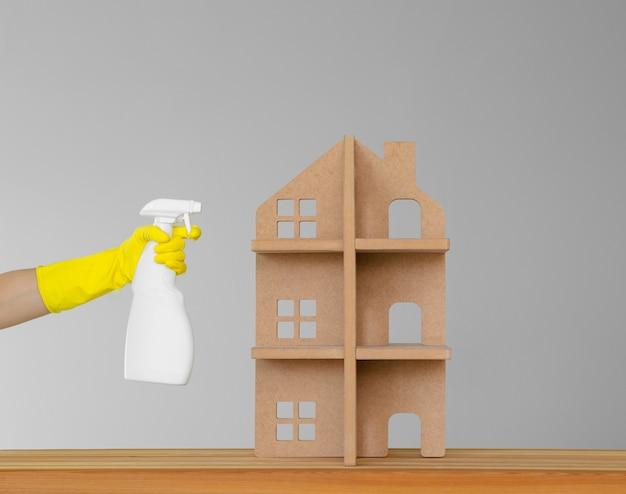Houten speelgoedhuis en een hand in een gele rubberhandschoen met een fles-nevel schoonmakende producten. het concept van de lente schoonmaak in het huis.