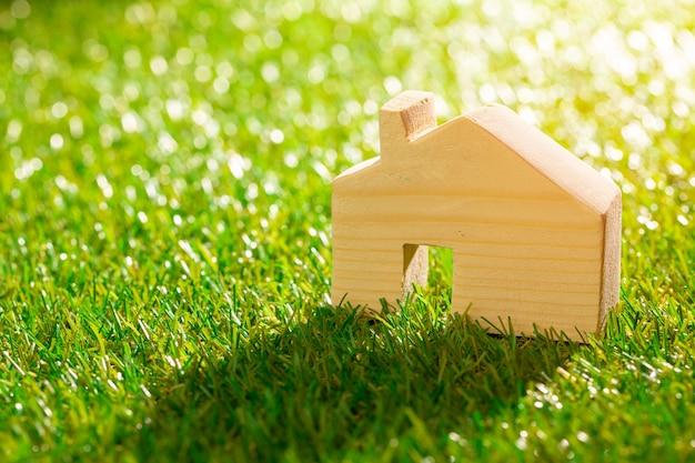 Houten speelgoedhuisminiatuur op gras