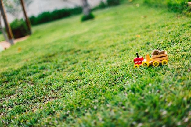 Houten speelgoedvrachtwagen die pakketten door het gazon of de aard vervoert