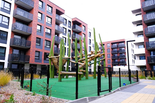 Houten speeltuin voor kinderen in een gezellige binnenplaats van moderne woonwijk.