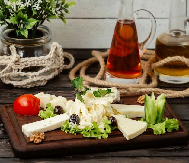 Houten standaard met gesneden kazen van verschillende soorten op de tafel