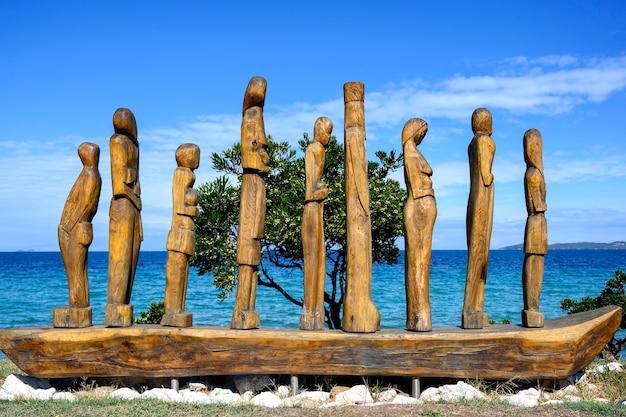 Houten standbeeld van mensen op een boot door de zee in nea roda, halkidiki, griekenland