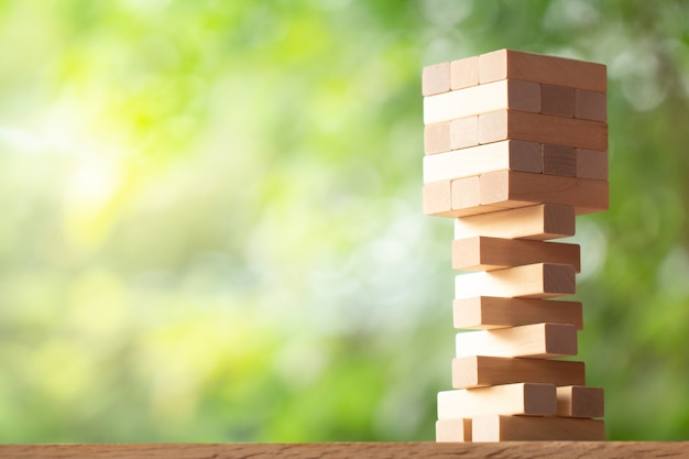 Houten stapel toren van houtsneden speelgoed op groen wazig achtergrond