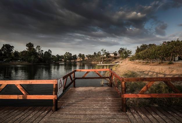 Houten steiger en tuinhuisje boven het meer in de mijn van sao domingos