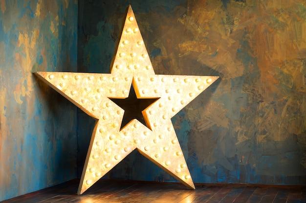 Houten ster met lichten die zich over rustieke muur bevinden