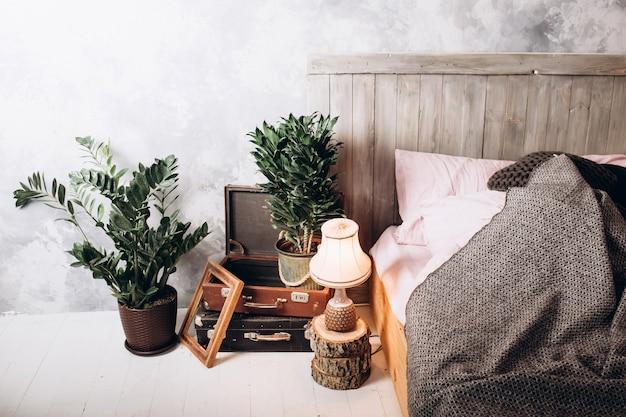 Houten stoel aan kaptafel in roze pastel slaapkamer interieur met gouden lamp naast bed