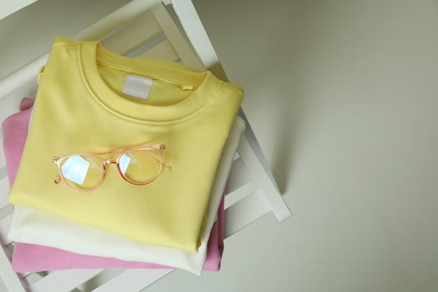 Houten stoel met gele, roze en witte sweatshirts en glazen