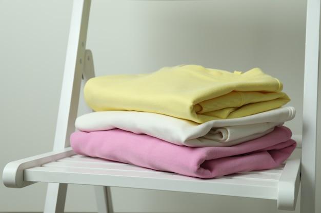 Houten stoel met gele, roze en witte sweatshirts