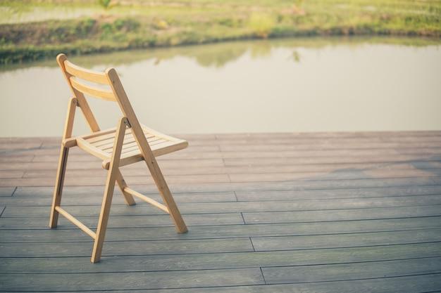 Houten stoel op balkonterras patio om uit te rusten bij vijver