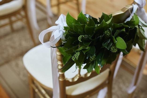 Houten stoel versierd met groene bladeren en witte strepen voor huwelijksceremonie