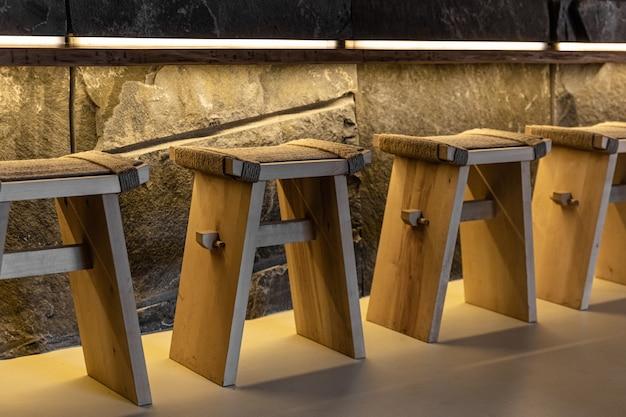 Houten stoelen met touw en stenen muur bij bar.