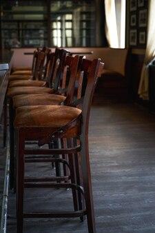 Houten stoelen naast toog op een rij. leeg café in de ochtend. portret oriëntatie