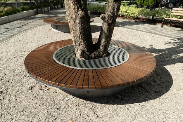 Houten stoelen rond een boom in een aangelegd park