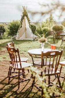 Houten stoffen wigwam versierd met groene eucalyptustakken in de achtertuin, het evenement of het huwelijk in bohostijl