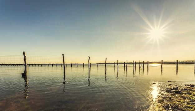 Houten stok en draadomheining op een meer