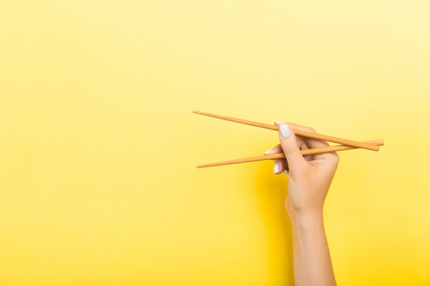Houten stokjes holded met vrouwelijke handen op geel. klaar voor het eten van concepten met lege ruimte