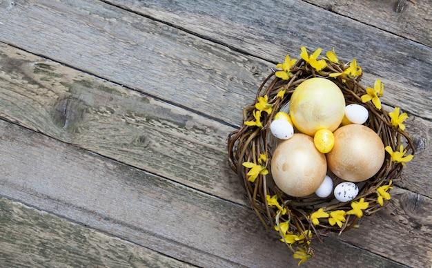 Houten structuur met gouden en gele eieren in een nest met bloemen. kopieer ruimte voor uw pasen-tekst