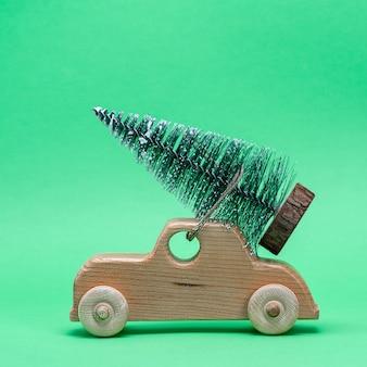 Houten stuk speelgoed auto die een feestelijke boom op het dak draagt