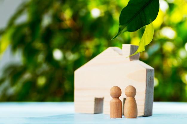 Houten stuk speelgoed huis en houten familie op gebladerteachtergrond dichte omhooggaand