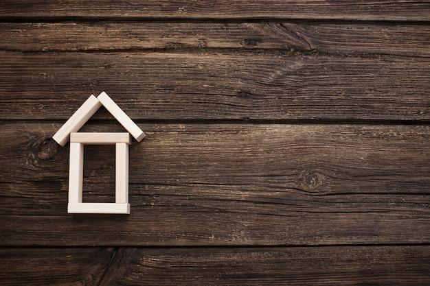 Houten stuk speelgoed huis op oude houten achtergrond