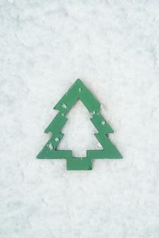 Houten stuk speelgoed in de vorm van een kerstboom op sneeuw