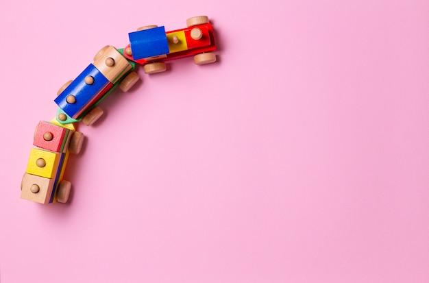 Houten stuk speelgoed trein op lichtroze achtergrond. bovenaanzicht