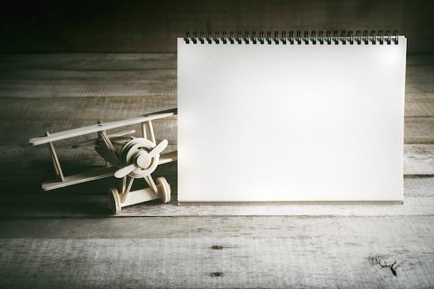 Houten stuk speelgoed vliegtuig met leeg notitieboekje op houten lijst met klaar exemplaarruimte