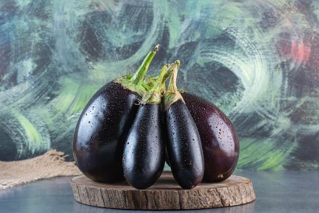 Houten stuk van natuurlijke verse aubergines op stenen oppervlak