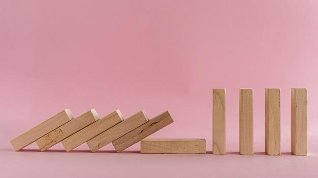 Houten stukken vallen op roze achtergrond
