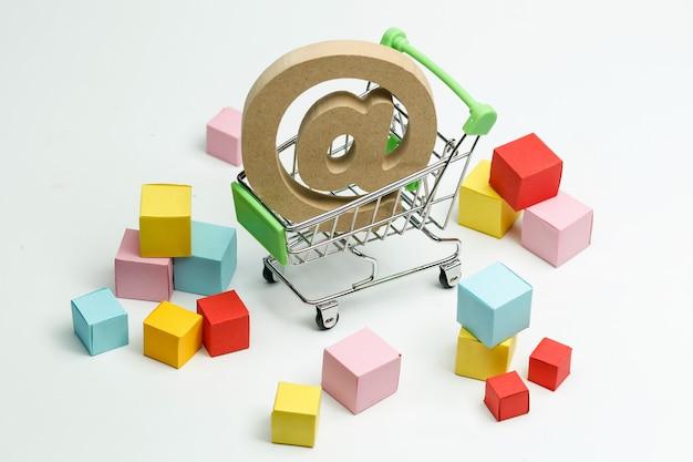 Houten symbool @ in winkelwagen, online winkelconcept