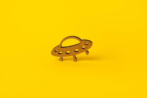 Houten symbool ufo op gele achtergrond