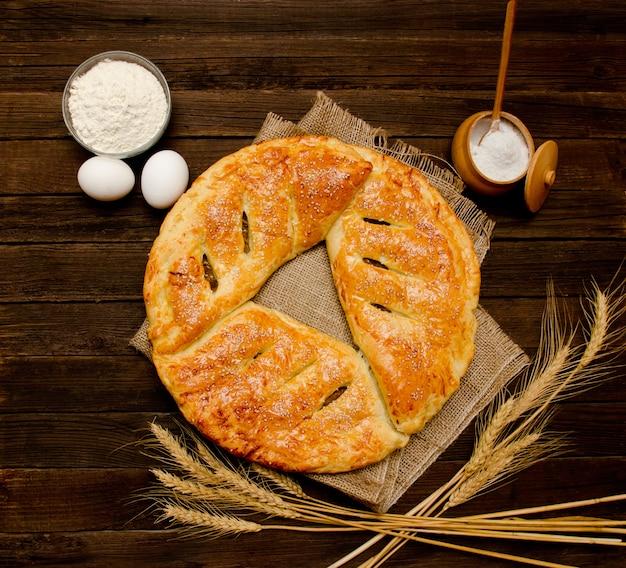 Houten taart op plundering. bakken ingrediënten: bloem, eieren, zout en oren. uitzicht van boven