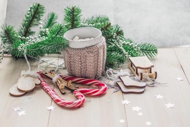 Houten tafel bedekt met snoepgoed, marshmallows en kerstversieringen onder de lichten