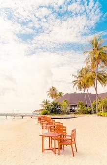 Houten tafel en stoel op het strand met uitzicht op zee in de maldiven