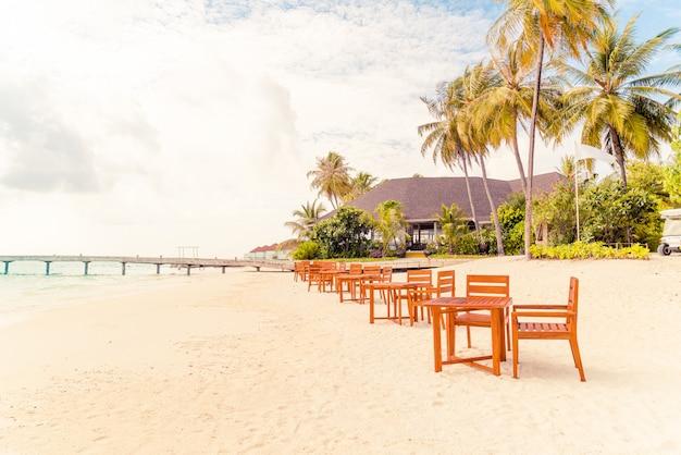 Houten tafel en stoel op strand met uitzicht op zee achtergrond in de maldiven